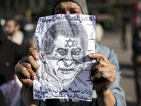 protestor holds up Mubarak's face with Star of David painted on his forehead