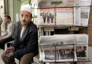 A Palestinian man sells newspapers in front of his shop in Gaza Strip